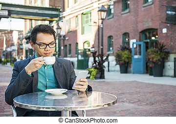Young asian man in outdoor cafe - Serious young asian man in...
