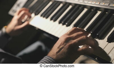 Man adjusts the synthesizer before the concert. Closeup