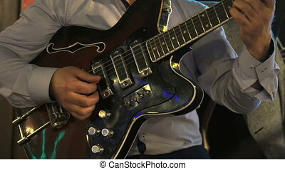 Guitarist playing on electric guitar in the club - Male...