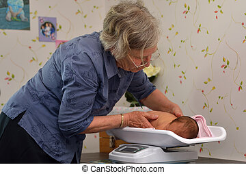midwife with baby - A senior midwife weighs a young baby as...