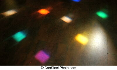 Disco light flashing different colors on the floor at night...