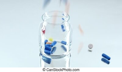 Colorful pills fall down into a bottle, on white, reflection...