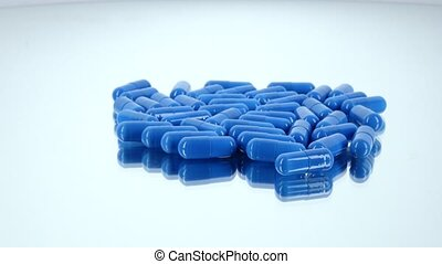 Medicine blue pills, on white, rotation, reflection -...