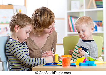 Kids playing with play clay at home or kindergarten or...