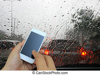 hand holding the smartphone on road view through car window...
