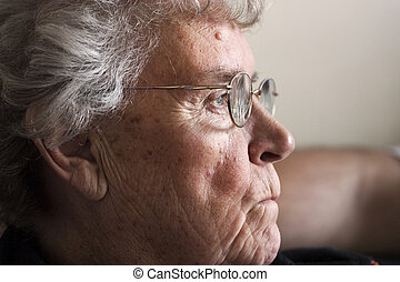 elderly lady in 70s viewed from side on with anxious or...