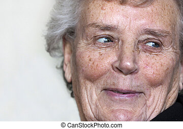 elderly woman smiling - natural shot of an elderly lady in...