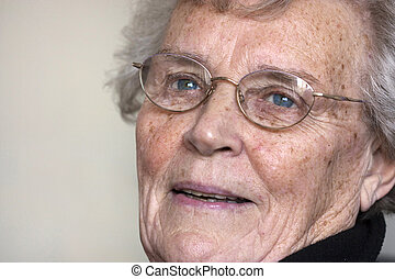 elderly woman gazing and smiling, aged 74 wearing glasses
