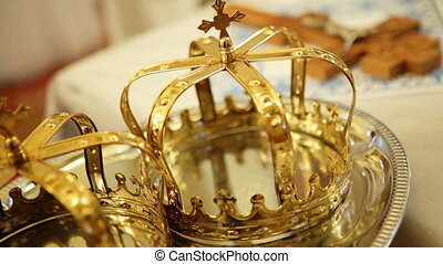 Close up of two gold wedding crowns prepared for ceremony of...