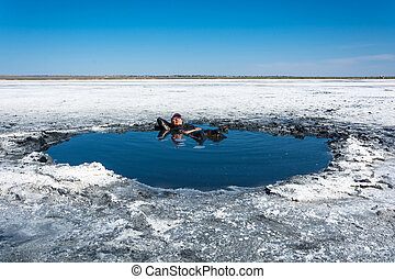 The woman accepts the curative mud baths on lake Elton - The...