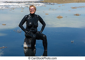 The woman accepts the curative mud baths on the lake...