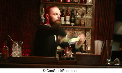 Handsome barman professional at posh bar making cocktail...