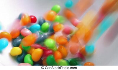 Jelly Beans Poured Into Bowl - Closeup of bright...