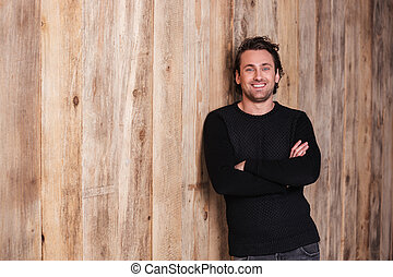 Smiling attractive man in black jumper standing with hands...