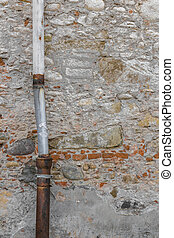 Old drainpipe - Detail of a downpipe against a brick wall.