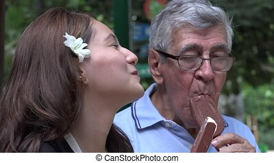 Teen Girl And Grandfather Eating Popsicles