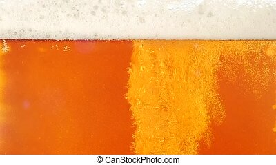 Light beer is poured in a glass. Closeup. Slow motion -...