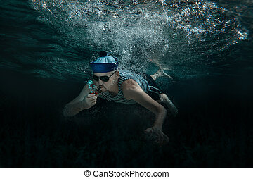 Man under water - Man swimming under water and smokes a pipe...
