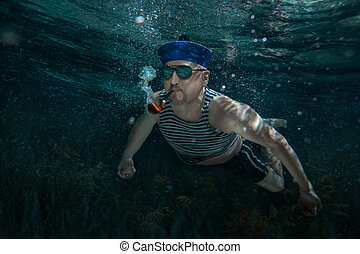 Man under water. - Seaman swims under water and smokes a...