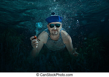Man under water. - Man swimming underwater sailor and smokes...