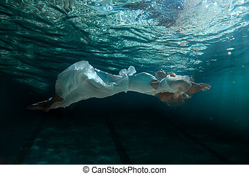 Woman in dress under water. - Woman in white dress swimming...