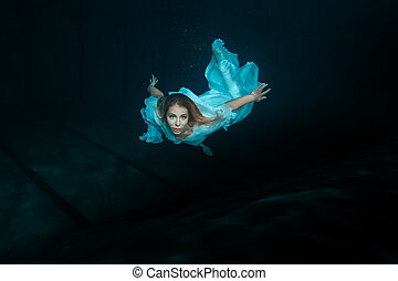 Woman mermaid under water. - A woman in a white dress as a...