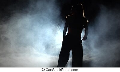 Girl shows karate techniques. Black. Silhouette. Backlight -...