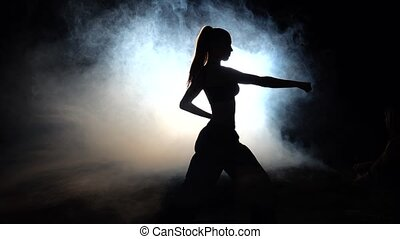 Girl athlete shows power moves. Black. Silhouette. Backlight...