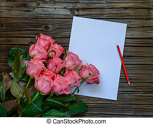 Dozen pink roses by pencil and paper on wood table - Dozen...
