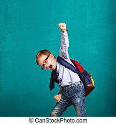 smiling little boy with big backpack jumping and having fun...