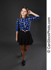 Full-lenght portrait of a girl in a plaid shirt and black...