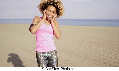 Happy young woman playing on the beach laughing with open...