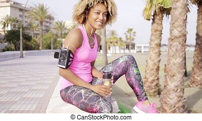 Sporty young woman relaxing with bottled water on the side...