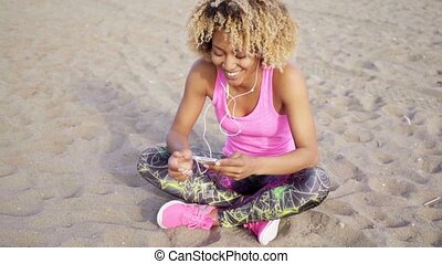 Woman sitting at beach listening to music - Single active...