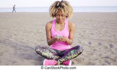 Trendy young woman listening to music on a beach sitting...