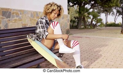 Young woman tying shoes with skateboard on bench - Serious...