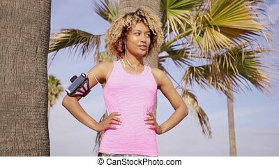 Confident fit woman with arm band music player - Confident...