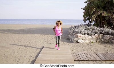 Fit young woman jogging on a beach - Fit young African woman...