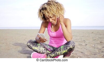 Grinning woman sitting on beach listening to music -...