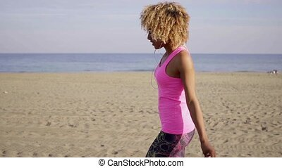 Happy woman dancing at beach - Smiling happy woman in frizzy...