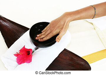 Hands of the masseur with a cup with aloe