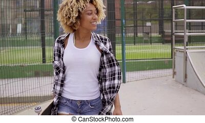 Sexy beautiful girl walking with skateboard in skate park
