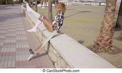 Happy trendy young woman with a skateboard sitting on a wall...