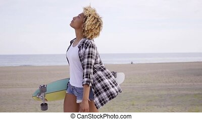 Sexy young woman carrying a skateboard at a beach - Sexy...