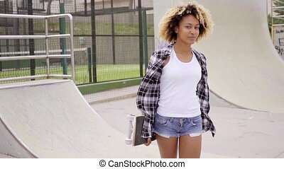 Pretty sporty young woman at a skating rink or park standing...