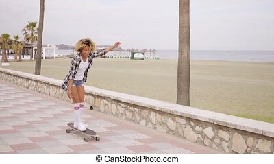 Young woman skateboarding at the seafront along a paved...