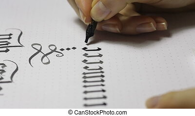 Writing Gothic calligraphy. female hand writes with ink pen.