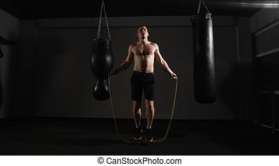 Young boxer training with a skipping rope as he practices...