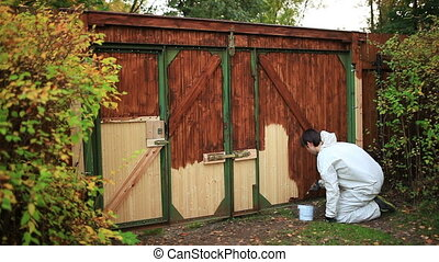 Man painting gate on country site fast motion