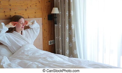 Young woman lying on bed and going to window